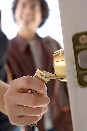 Hand unlocking door/ Stock Photo - Premium Royalty-Free, Code: 604-00941478
