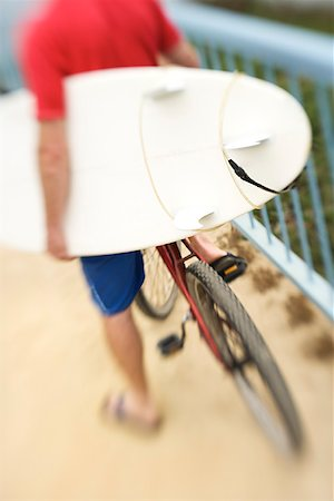 Man with surfboard on bicycle/ Stock Photo - Premium Royalty-Free, Code: 604-01002573