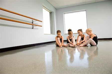 Ballet students adjusting slippers Stock Photo - Premium Royalty-Free, Code: 604-01119424