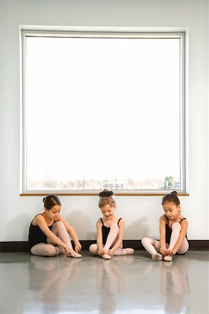 Ballet students sitting by window adjusting slippers Stock Photo - Premium Royalty-Free, Code: 604-01119422