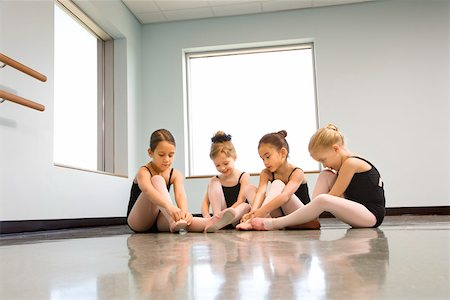 Ballet students adjusting slippers Stock Photo - Premium Royalty-Free, Code: 604-01119423