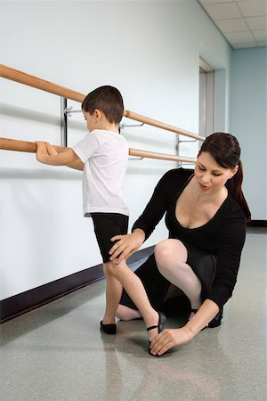 Ballet instructor correcting boy's position Stock Photo - Premium Royalty-Free, Code: 604-01119441