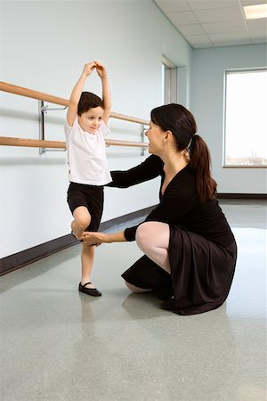Ballet instructor correcting boy's position Stock Photo - Premium Royalty-Free, Code: 604-01119442