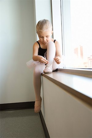 Girl sitting in window adjusting ballet slippers Stock Photo - Premium Royalty-Free, Code: 604-01119466