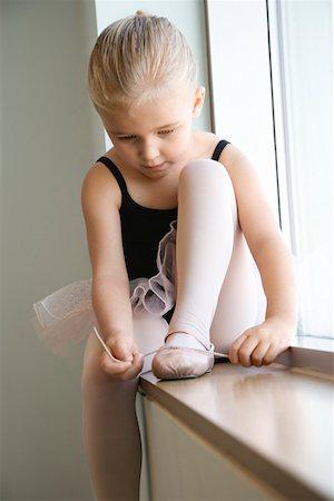 Girl sitting in window adjusting ballet slippers Stock Photo - Premium Royalty-Free, Code: 604-01119467