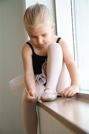 Girl sitting in window adjusting ballet slippers Stock Photo - Premium Royalty-Free, Code: 604-01119467
