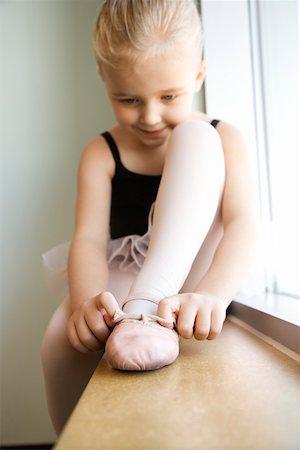 Girl sitting in window adjusting ballet slippers Stock Photo - Premium Royalty-Free, Code: 604-01119469