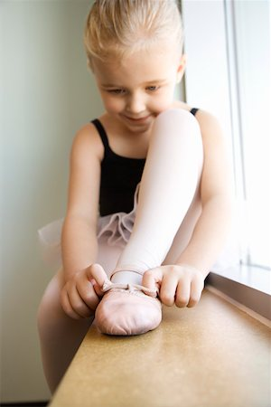 Girl sitting in window adjusting ballet slippers Stock Photo - Premium Royalty-Free, Code: 604-01119469