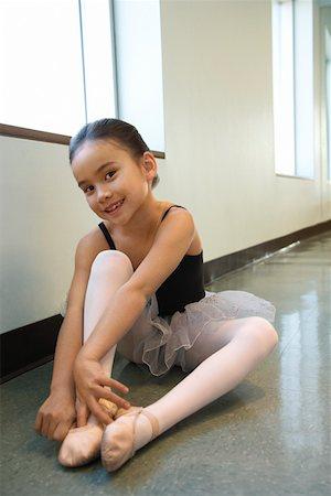preteen models asian - Girl sitting on floor adjusting ballet slippers Stock Photo - Premium Royalty-Free, Code: 604-01119475