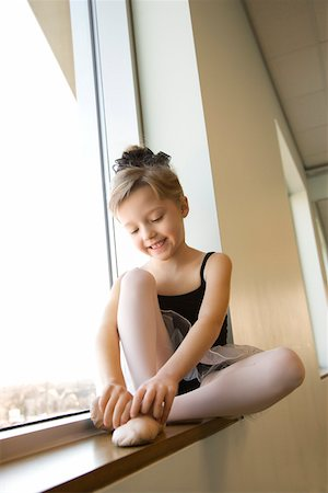 Girl sitting in window adjusting ballet slippers Stock Photo - Premium Royalty-Free, Code: 604-01119472
