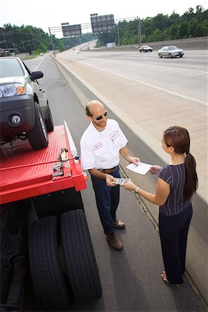 Woman paying tow truck driver Stock Photo - Premium Royalty-Free, Code: 604-01231578