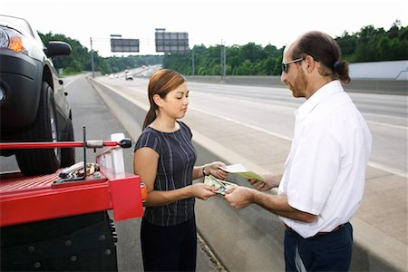 Woman paying tow truck driver Stock Photo - Premium Royalty-Free, Code: 604-01232255