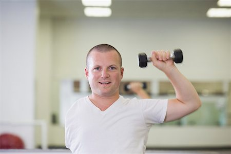 One-armed man lifting weight at gym Stock Photo - Premium Royalty-Free, Code: 604-01569856