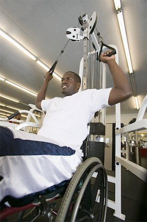 Man in wheelchair exercising at gym Stock Photo - Premium Royalty-Free, Code: 604-01569857