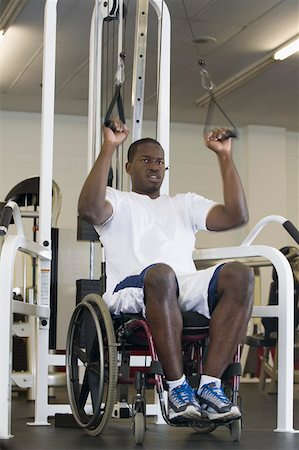 Man in wheelchair at exercise machine Stock Photo - Premium Royalty-Free, Code: 604-01569859