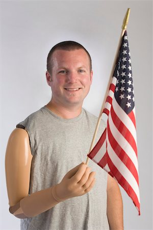 Man with prosthetic arm holding american flag Stock Photo - Premium Royalty-Free, Code: 604-01569885