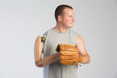 Man with prosthetic arm and baseball glove Stock Photo - Premium Royalty-Free, Code: 604-01569887