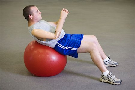 Man with prosthetic arm on exercise ball Stock Photo - Premium Royalty-Free, Code: 604-01569894