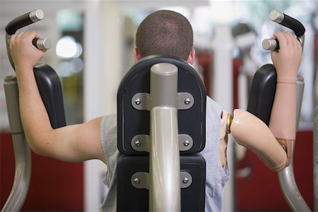 Rear view of man with prosthetic arm in gym Stock Photo - Premium Royalty-Free, Code: 604-01569890