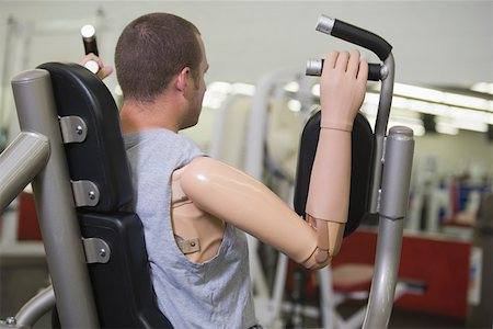 Man with prosthetic arm in gym Stock Photo - Premium Royalty-Free, Code: 604-01569891