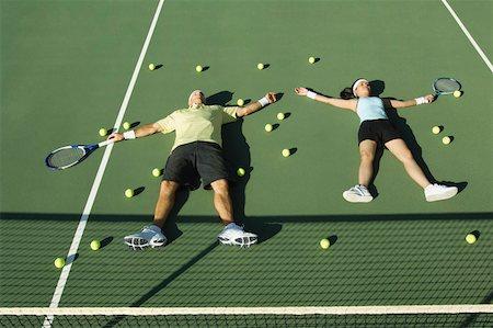 Tennis players lying down on tennis court Stock Photo - Premium Royalty-Free, Code: 604-01826882