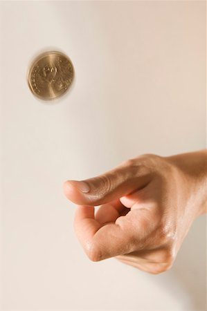 Hand flipping coin Stock Photo - Premium Royalty-Free, Code: 604-01878544