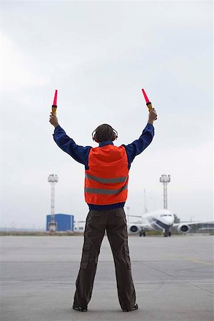 Rear view of airport hangar worker directing plane on tarmac Stock Photo - Premium Royalty-Free, Code: 604-02288698
