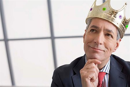 Businessman with crown thinking Stock Photo - Premium Royalty-Free, Code: 604-02370593