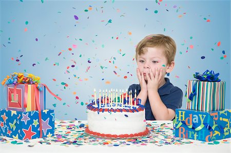 Young Boy with Birthday Presents and Making a Wish before Blowing Out Candles on Birthday Cake Stock Photo - Premium Royalty-Free, Code: 600-04223481