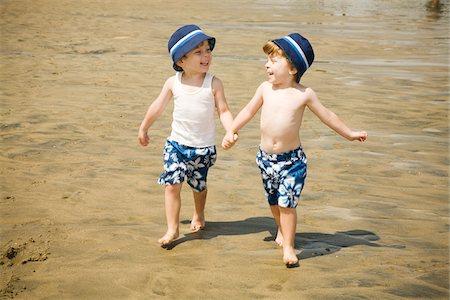 Twin Boys Walking Hand in Hand on Beach Stock Photo - Premium Royalty-Free, Code: 600-04223559