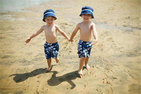 Twin Boys Walking Hand in Hand on Beach Stock Photo - Premium Royalty-Free, Code: 600-04223560
