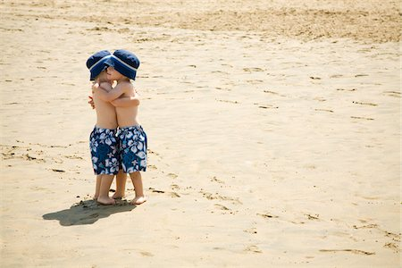 Twin Boys Hugging on Beach Stock Photo - Premium Royalty-Free, Code: 600-04223561