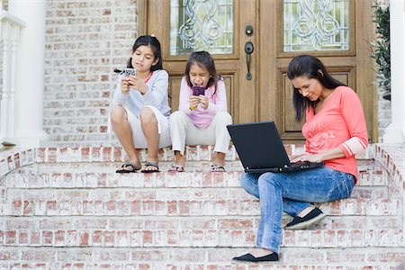 family shoes - Mother using Laptop and Daughters using Handheld Video Games Stock Photo - Premium Royalty-Free, Code: 600-04625356