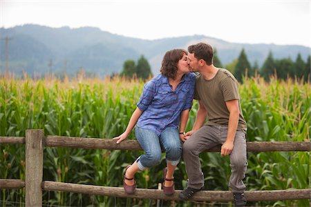 Couple Sitting on Fence Kissing, Sauvie Island, Oregon, USA Stock Photo - Premium Royalty-Free, Code: 600-04931708