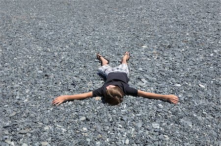 Boy Lying Down on the Ground, Corsica, France Stock Photo - Premium Royalty-Free, Code: 600-05181844