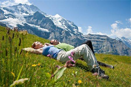 Couple Sitting on Mountain Side, Bernese Oberland, Switzerland Stock Photo - Premium Royalty-Free, Code: 600-05452093