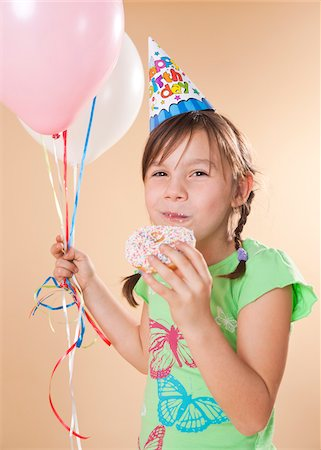 preteen girl pigtails - Portrait of Girl Eating Doughnut Stock Photo - Premium Royalty-Free, Code: 600-05653081