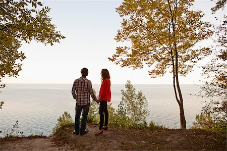 Backview of Young Couple Standing at Edge of Cliff Looking out at View, Ontario, Canada Stock Photo - Premium Royalty-Free, Code: 600-05786160