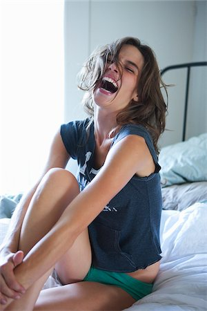 Woman Sitting on Bed Laughing Stock Photo - Premium Royalty-Free, Code: 600-05803534