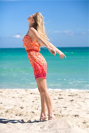 Woman Standing on Beach Feeling the Breeze Stock Photo - Premium Royalty-Free, Code: 600-05822160
