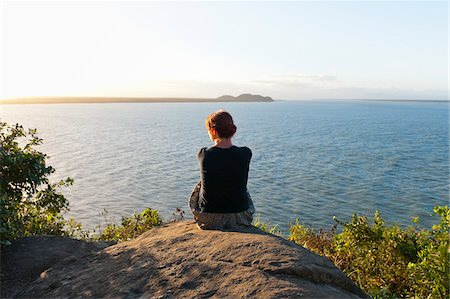 Backview of Woman Sitting on Hill, Ilha do Mel, Parana, Brazil Stock Photo - Premium Royalty-Free, Code: 600-05947927