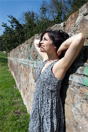 Woman Leaning against Wall Stock Photo - Premium Royalty-Free, Code: 600-05948137