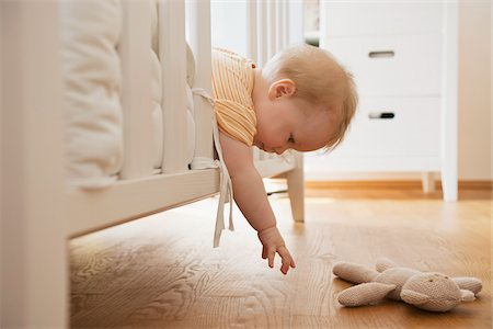 Baby Girl Reaching out of Crib to get Stuffed Toy Stock Photo - Premium Royalty-Free, Code: 600-05973076
