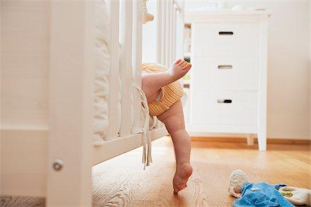 Baby Girl Climbing into Crib Stock Photo - Premium Royalty-Free, Code: 600-05973073