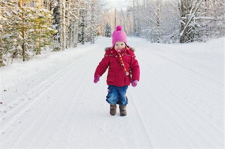 Portrait of Little Girl Walking Down Road in Winter Stock Photo - Premium Royalty-Free, Code: 600-05973087