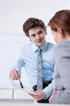 Young Businessman giving Presentation to Businesswoman Stock Photo - Premium Royalty-Free, Code: 600-05973117