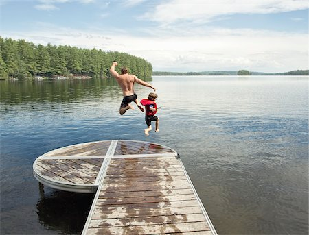Father and Son Jumping in Lake, Belgrade Lakes, Maine, USA Stock Photo - Premium Royalty-Free, Code: 600-05973263