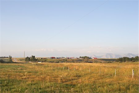 Prairie Farm and Fields, Rocky Mountains in Distance, Utopia Farm, Pincher Creek, Alberta, Canada Stock Photo - Premium Royalty-Free, Code: 600-05973415
