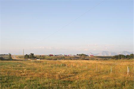 Prairie Farm and Fields, Rocky Mountains in Distance, Utopia Farm, Pincher Creek, Alberta, Canada Stock Photo - Premium Royalty-Free, Code: 600-05973415