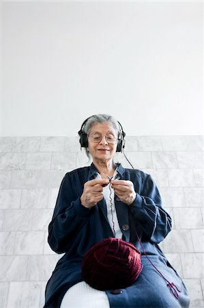 Woman Knitting and Listening to Headphones Stock Photo - Premium Royalty-Free, Code: 600-06144860